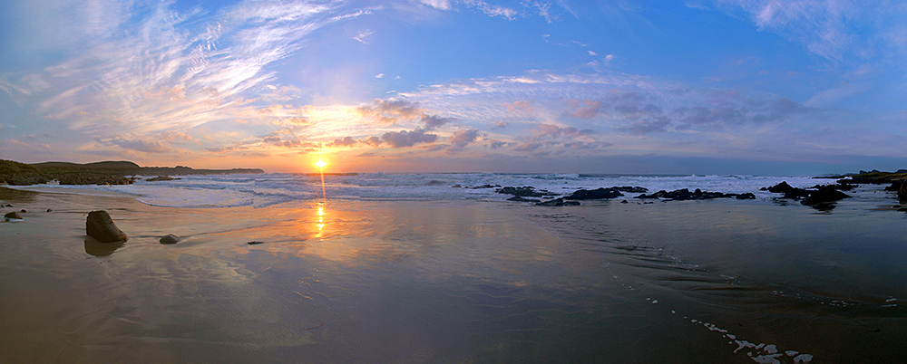 Panoramic picture of a sunset in a bay with a beach