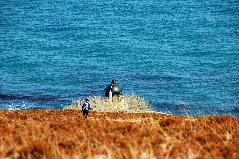 Picture of a walker descending a steep hill towards a lighthouse, only the top of the lighthouse is visible
