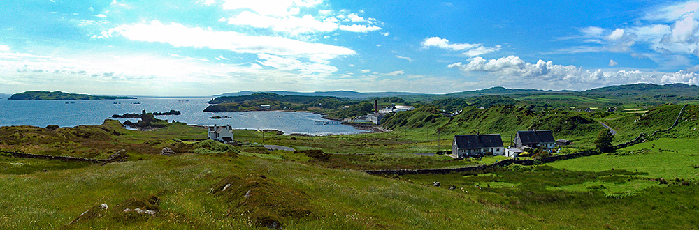 Panoramic picture of a view over a bay with a castle ruin and a distillery, also an island offshore