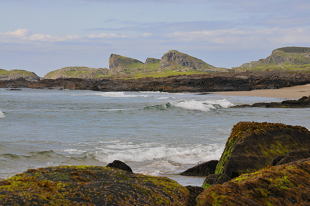 Picture of a small wave breaking in a bay with both rocky shore and beach