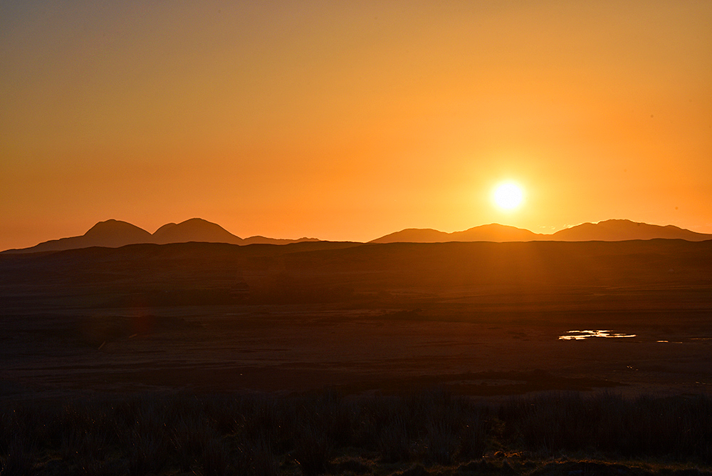 Picture of a sunrise over a hilly landscape