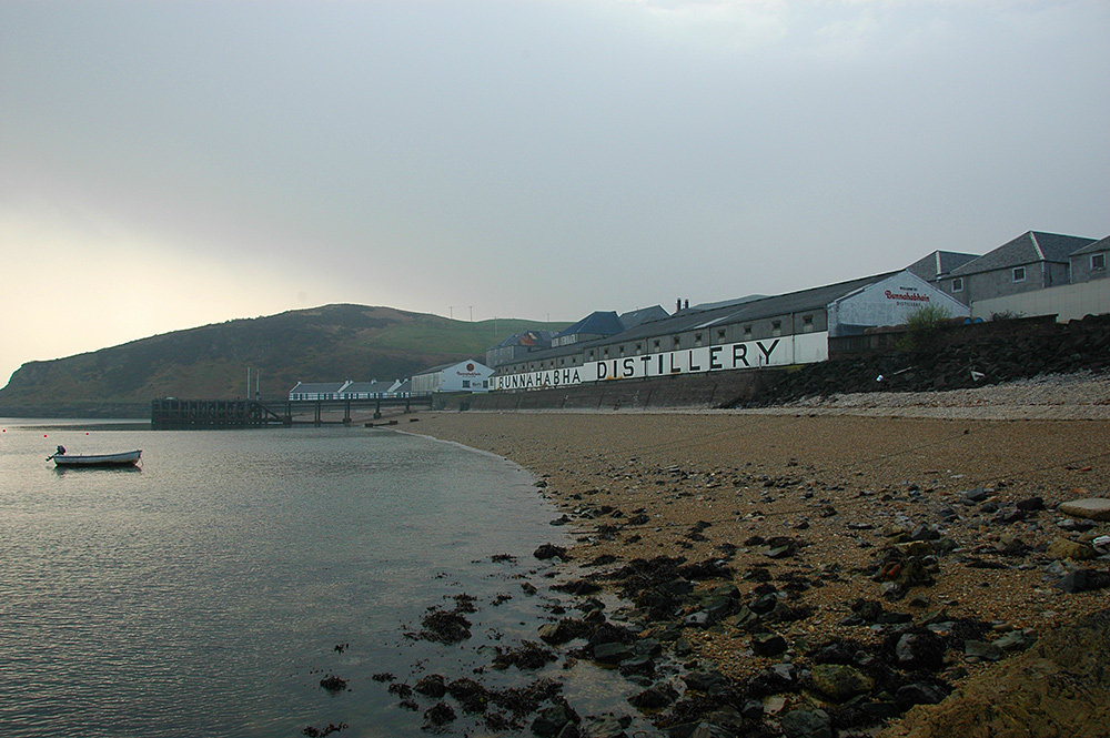 Picture of Bunnahabhain distillery from the shore below the distillery on an overcast morning