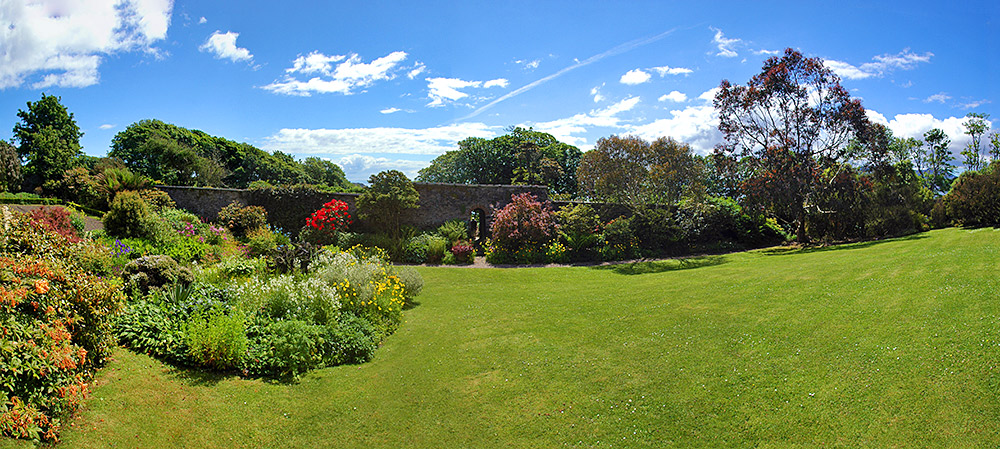 Panoramic picture of a lawn bordered by flower beds in a walled garden