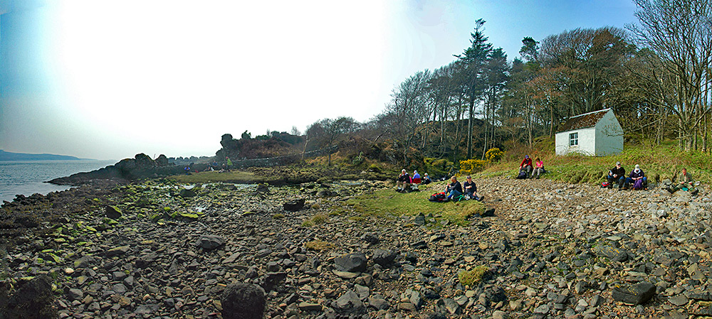 Panoramic picture of a group of walkers taking a lunch break next to a sound between two islands
