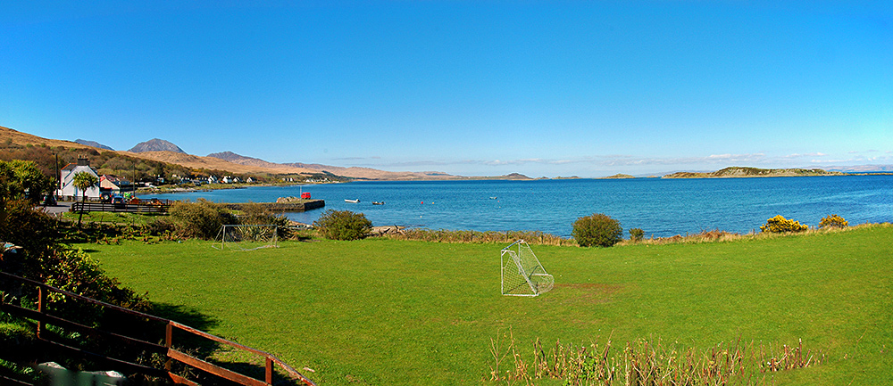 Panoramic picture of a bay with sheltering islands, seen from a hotel garden with a small football pitch