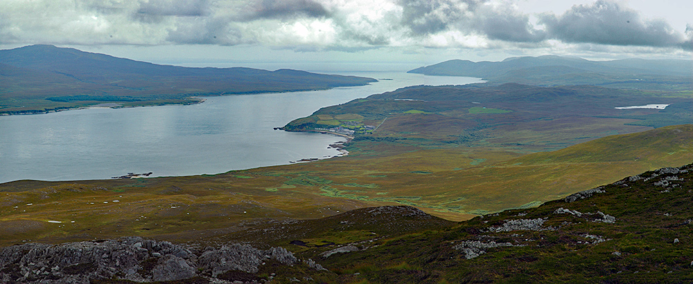 Picture of a view over a sound between two islands from a hill, a coastal distillery just visible