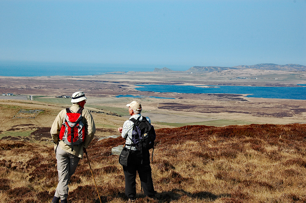 Picture of two men on a hill overlooking a loch and the sea on a hazy day