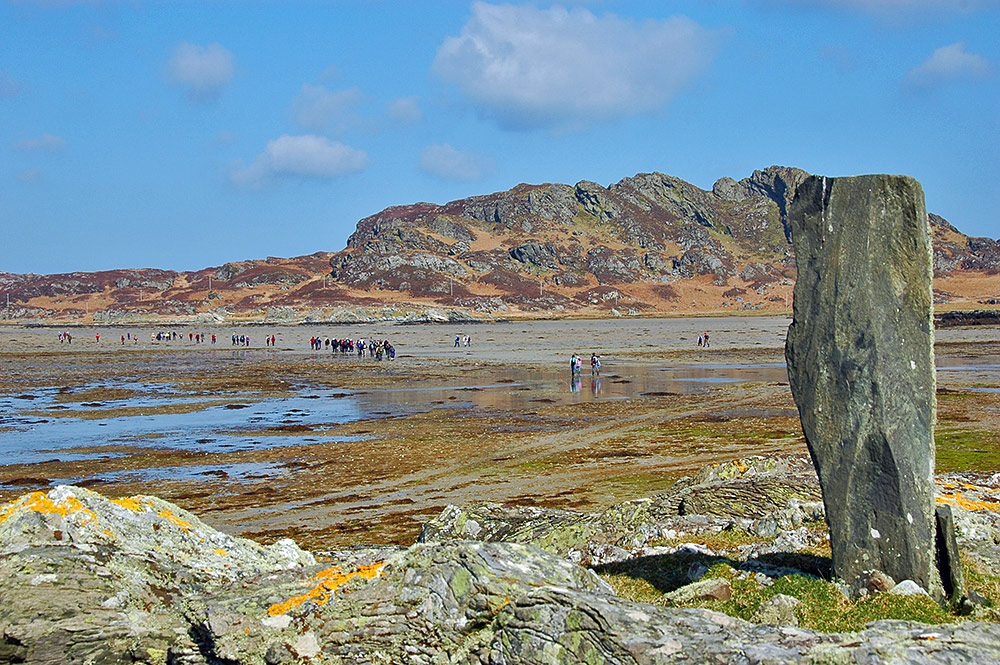 Picture of a large group of walkers on a beach at low tide between two islands