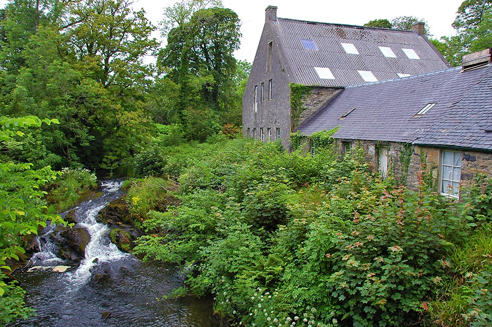 Picture of an old woollen mill next to a river running down rapids