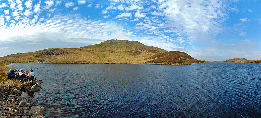 Panoramic picture of a group of walkers enjoying a picnic on the shore of a loch (lake)