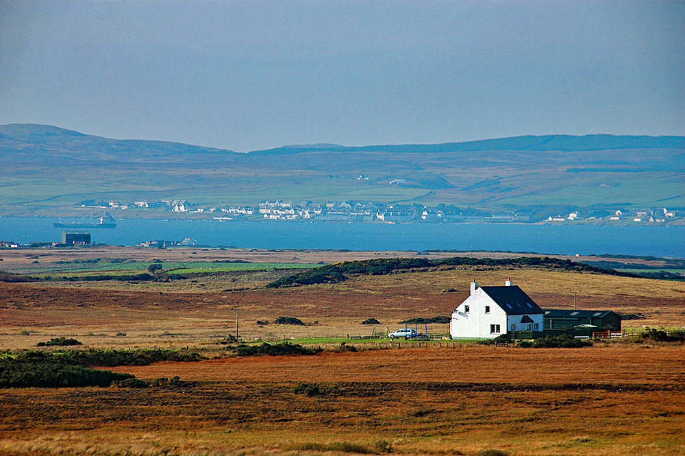 Picture of a distant coastal village, seen across a sea loch and some land