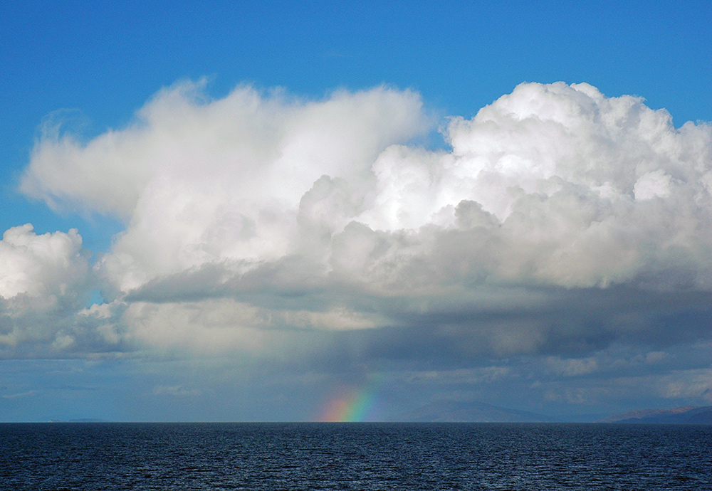 Picture of a heavy rain shower over the sea, a small rainbow below the clouds