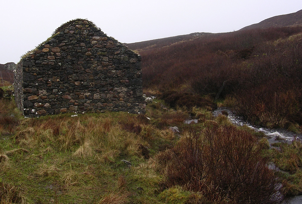 Picture of an old ruin in the rain, a stream flowing close past it