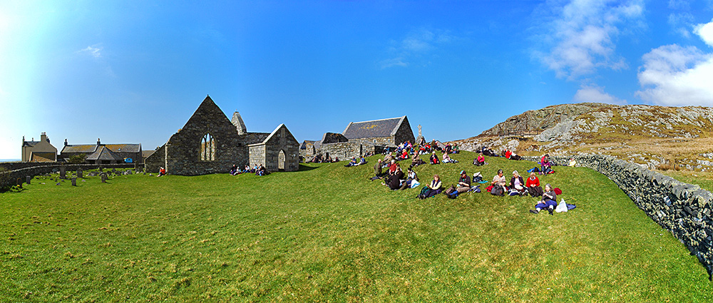 Picture of a large group of walkers resting on the ground of an old priory