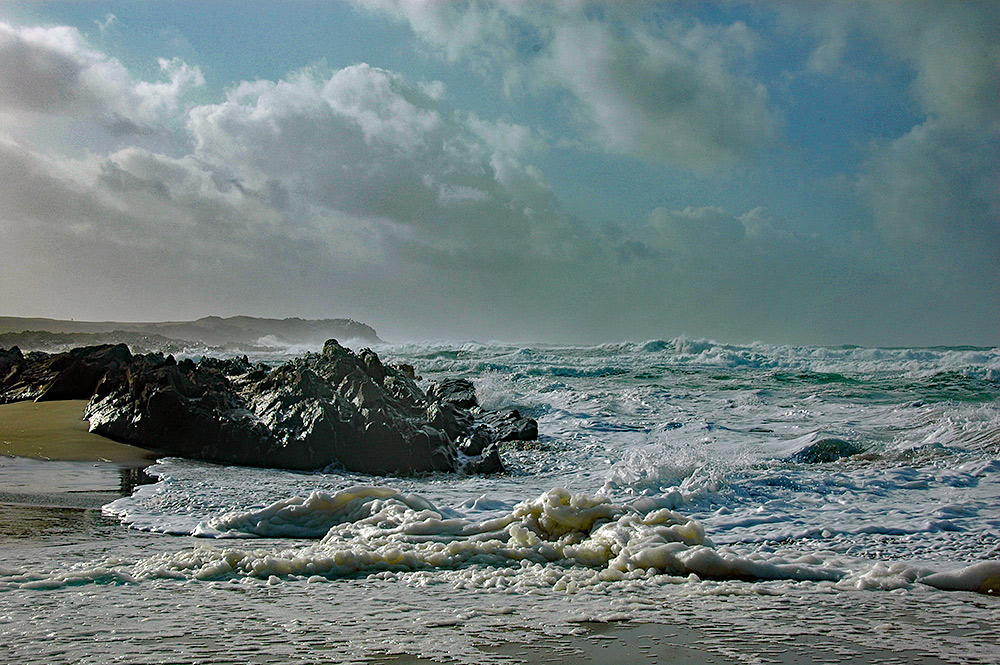 Picture of a beach on a stormy day, foam being washed up the beach