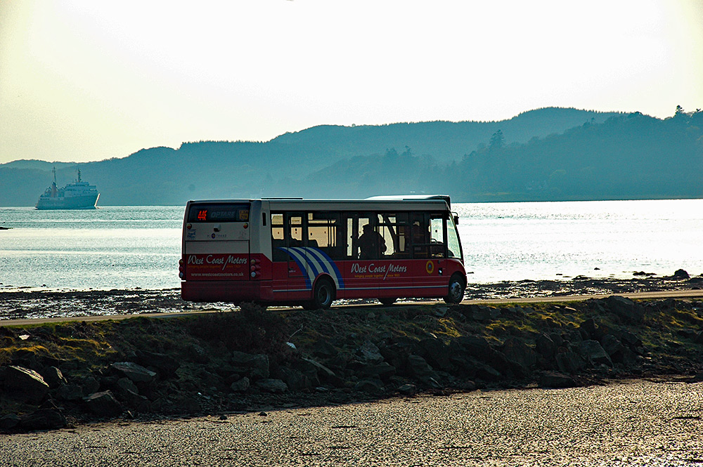 Picture of a small coach crossing a causeway to a ferry terminal, a ferry arriving in the background