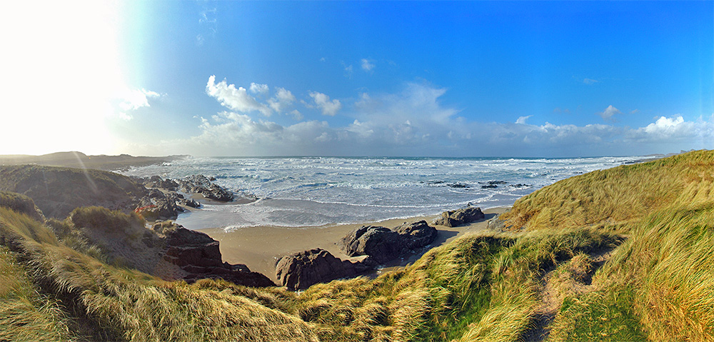 Panoramic picture of a bay with dunes and beach on a windy October afternoon
