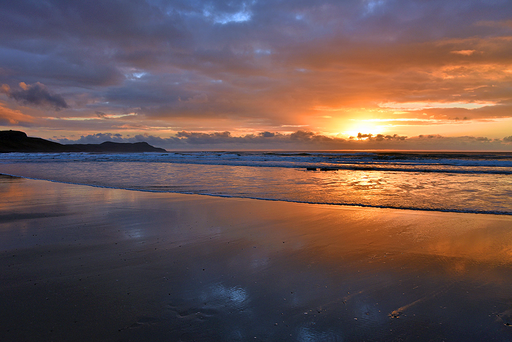 Picture of a colourful dramatic cloudy sunset in a bay with a beach