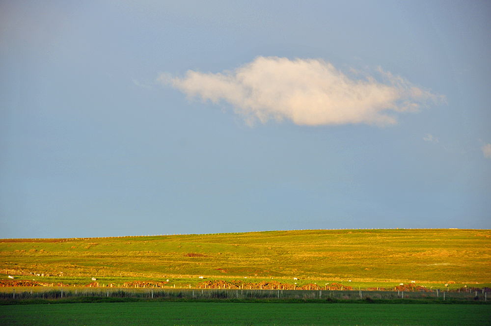Picture of a single light cloud over a low hill in the June evening light