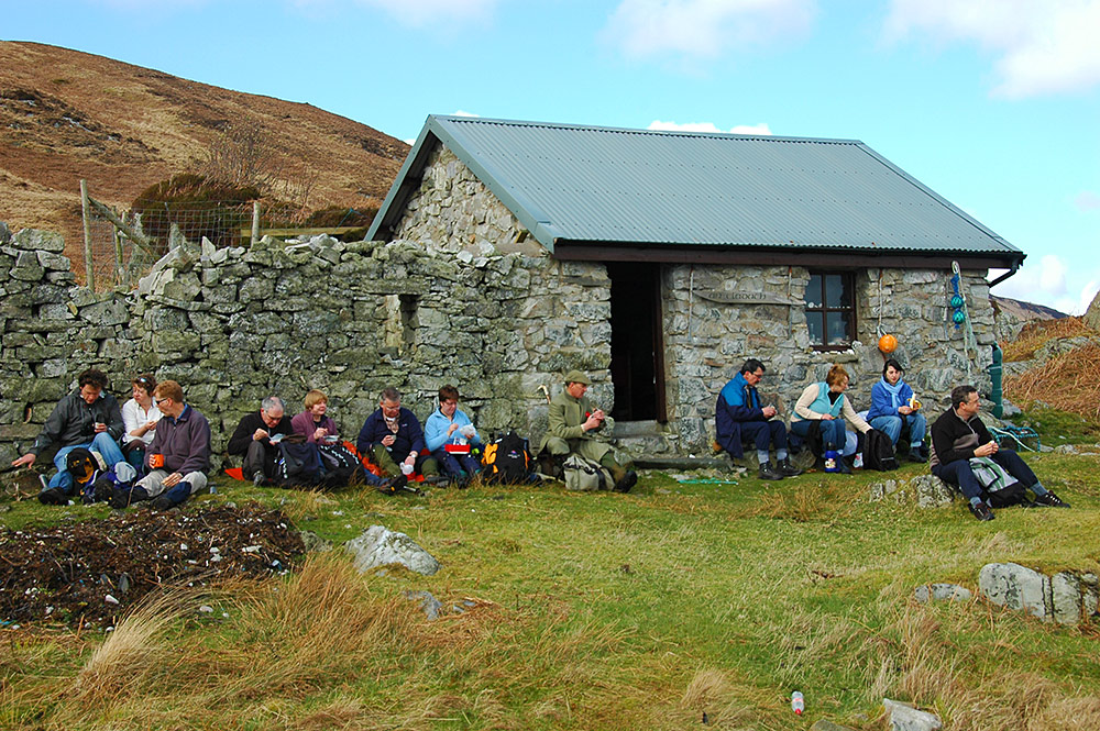 Picture of a group of walkers enjoying their lunch outside a small bothy