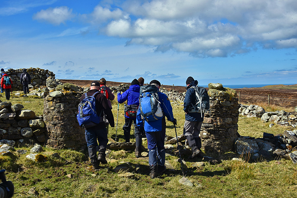 Picture of a group of walkers passing through a ruined old gate at an abandoned farm