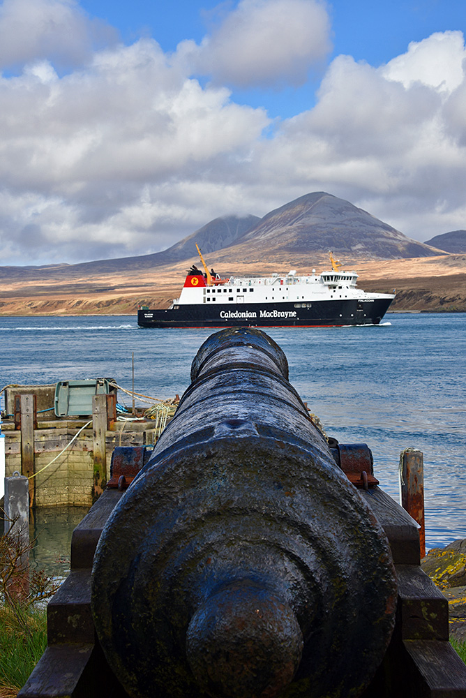 Picture of an old cannon pointing at a modern ferry