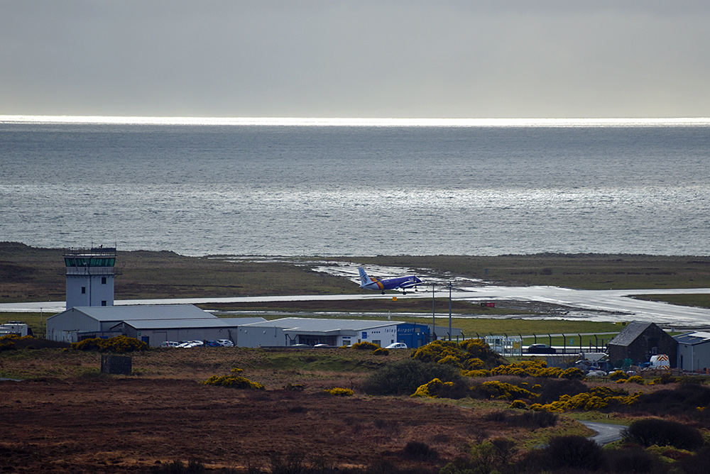Picture of a small passenger plane taking off from a rural airport at a coast