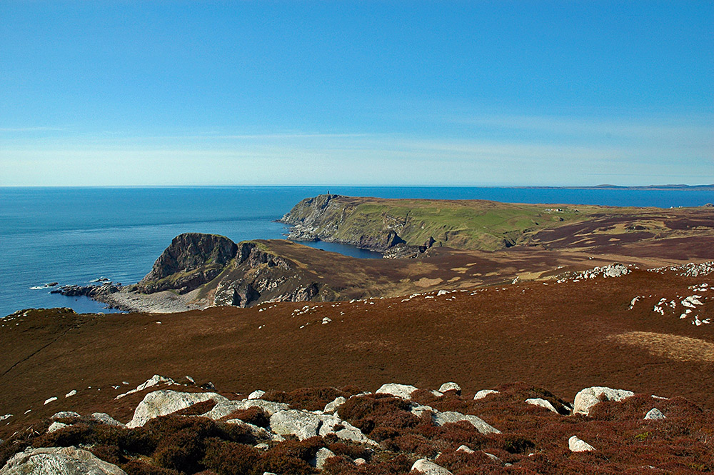 Picture of a coastal landscape with steep cliffs seen from the highest hill in the area