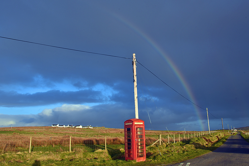 Picture of a red phone box at a single track road with a rainbow above