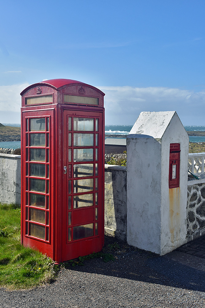 Picture of a red phone box next to a wall with a post box, overlooking a coast