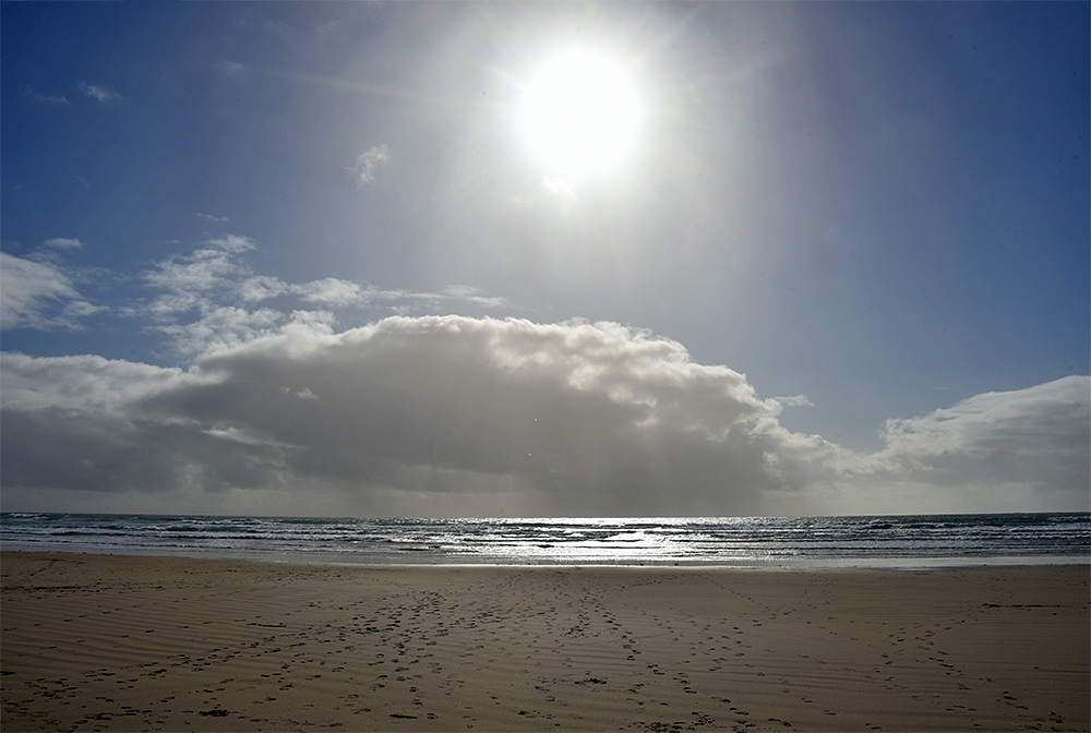 Picture of the bright Sun over a distant shower, seen from a beach