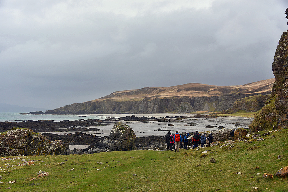 Picture of a group of walkers arriving at a remote beach on a grey and overcast day