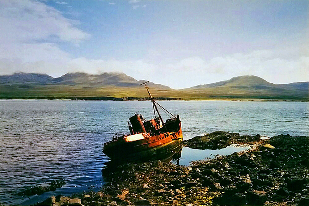 Picture of the wreck of a fishing trawler stranded on a rocky shore