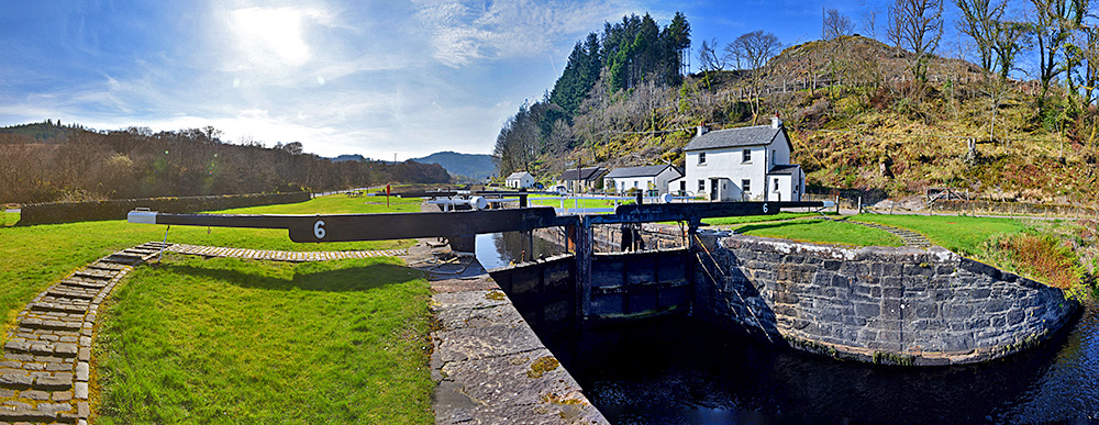 Panoramic picture of a canal lock with a row of houses next to it