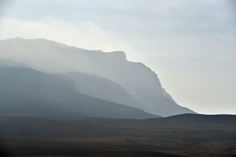 Picture of the silhouettes of a few hills on a hazy day