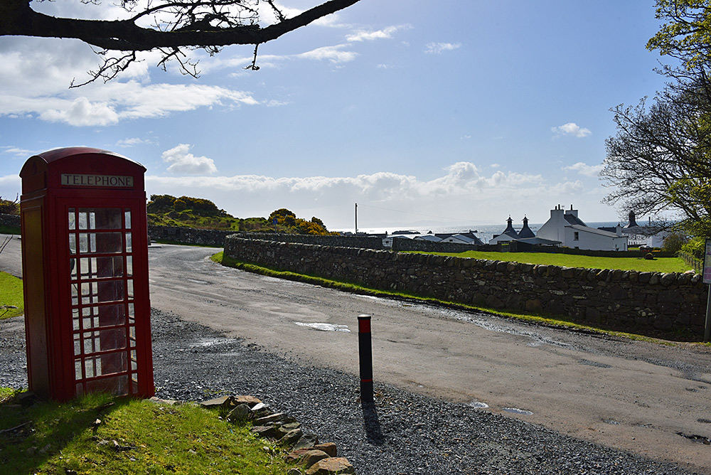 Picture of a red phone box next to a path and a road, a distillery in the background