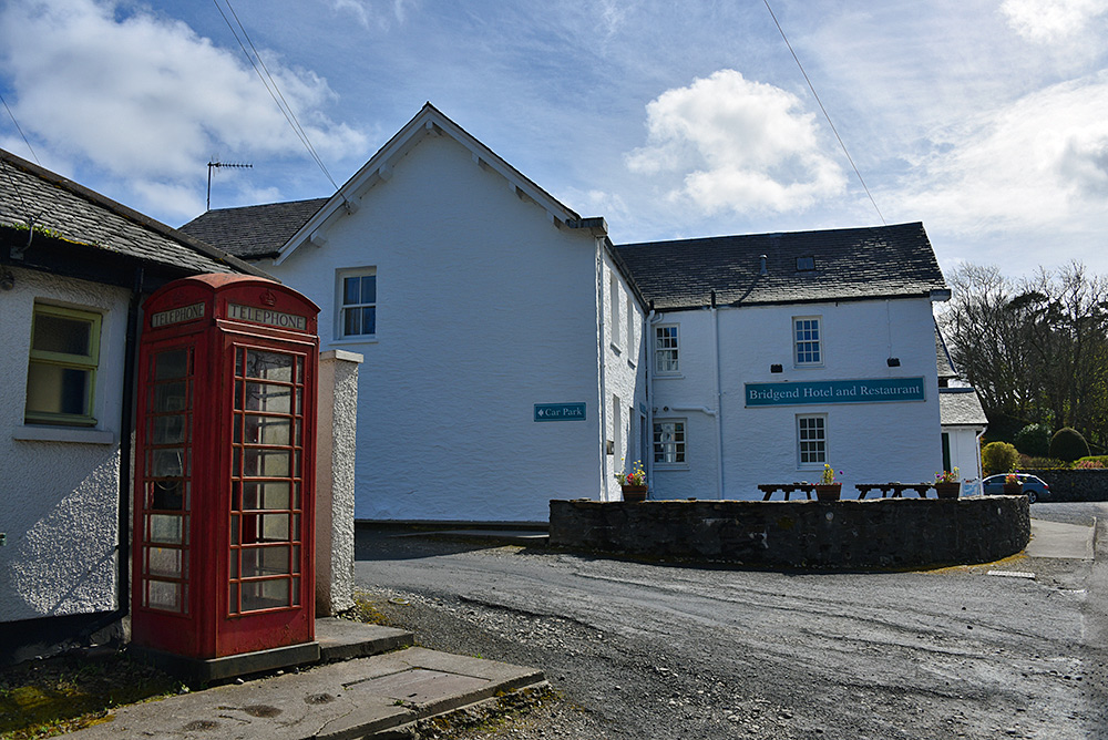 Picture of a red phone box next to a bus shelter and a hotel