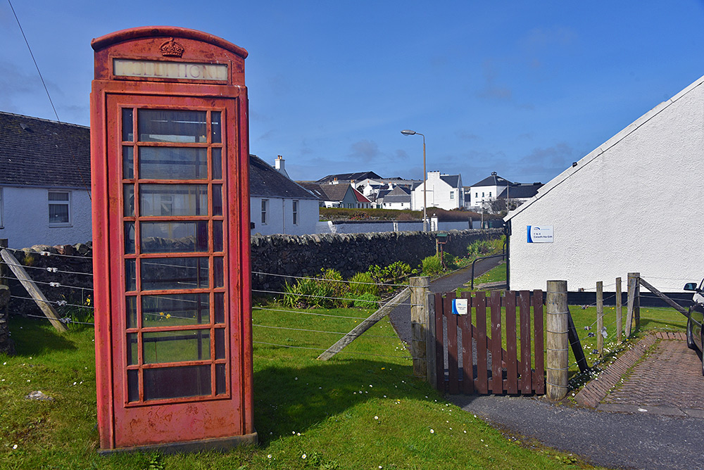 Picture of an old style red phone box on a village road