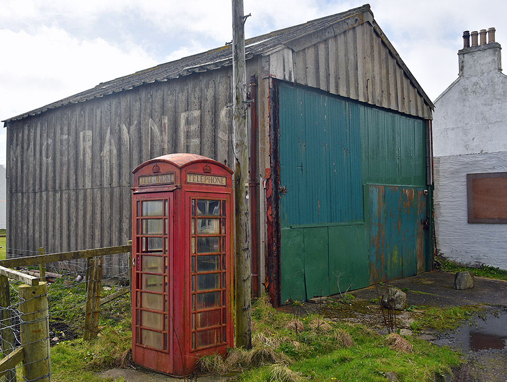 Picture of an old red phone box next to an old garage/shed with the fading name MacBraynes painted on the side