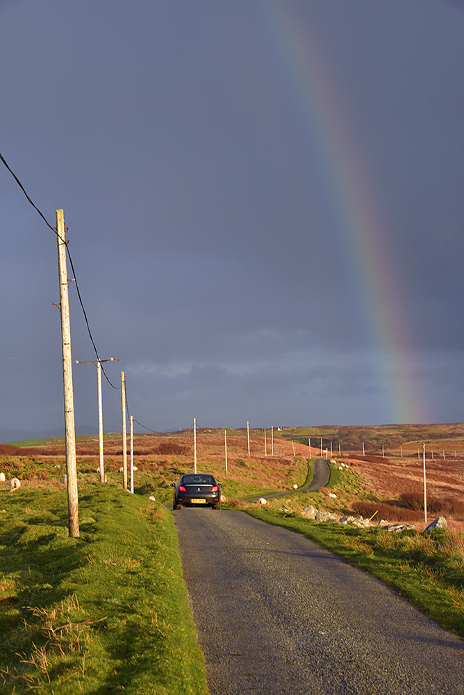 Picture of a single track road leading into the distance towards a rainbow