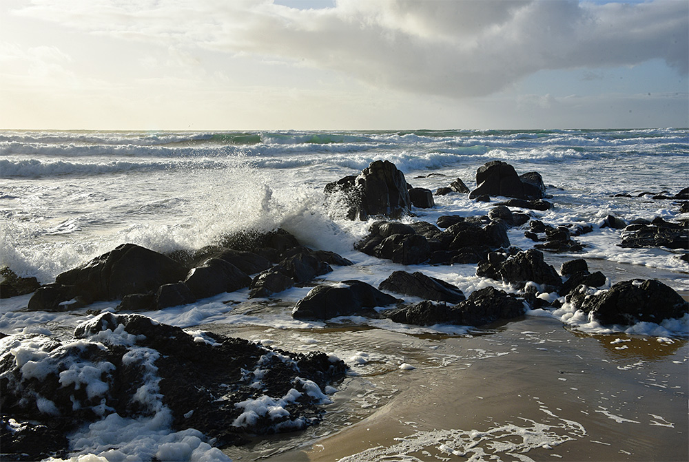Picture of waves breaking over rocks in a sandy beach, some foam also visible