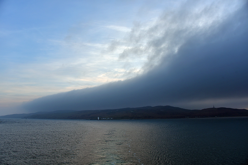 Picture of some very dark clouds over a peninsula seen from a ferry