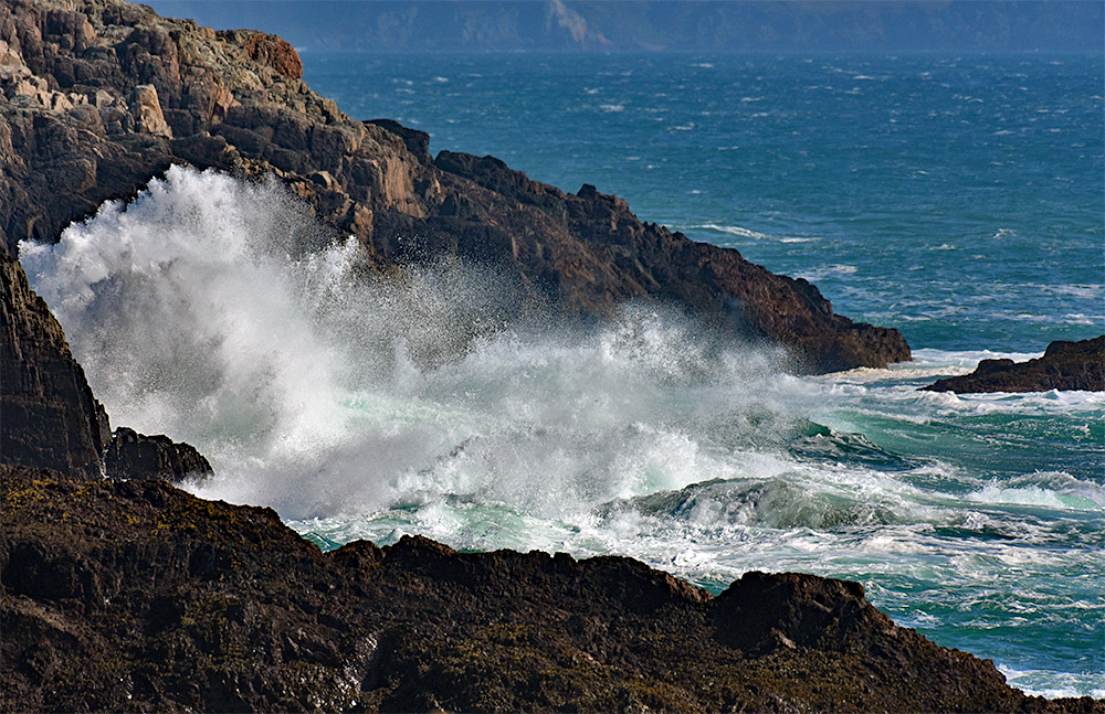 Picture of a wave breaking at a rocky shore, sending spray up into the air