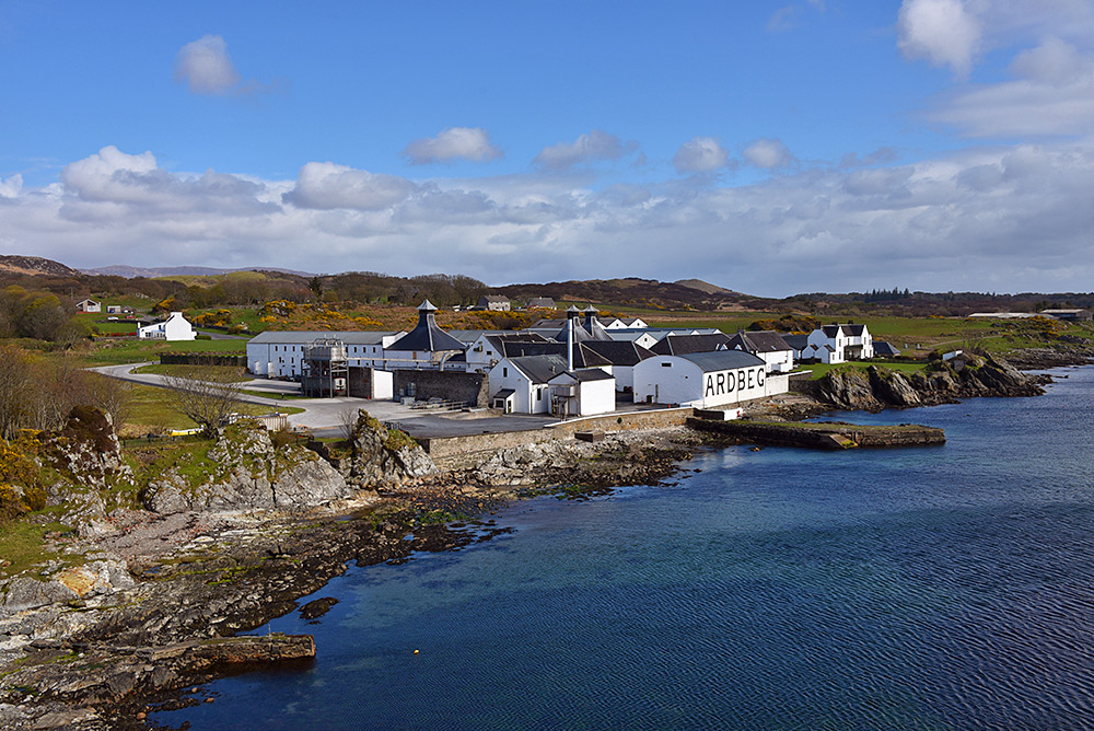 Picture of Ardbeg distillery seen from the low hills down the shore