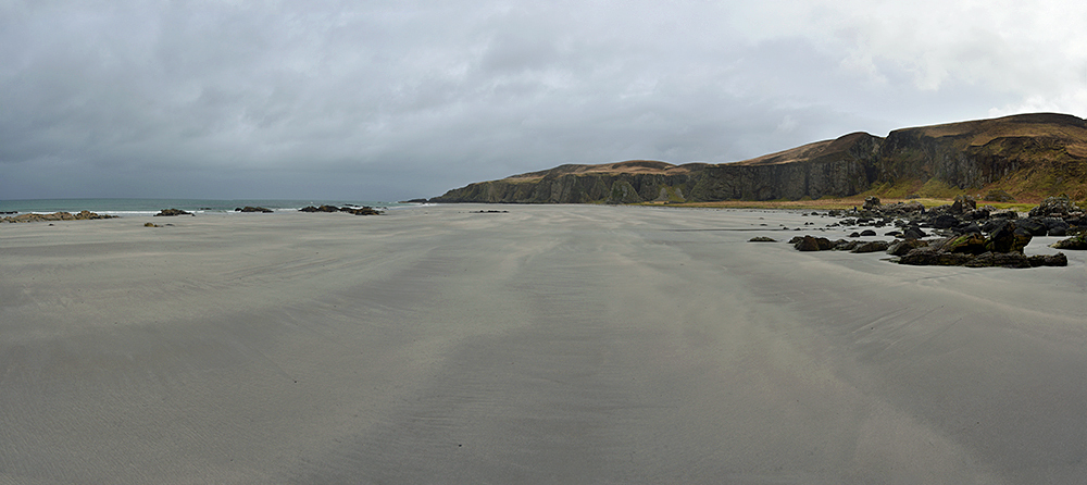 Panoramic picture of a remote beach under a cloudy sky