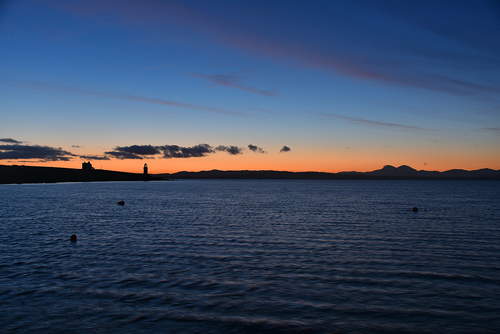 Picture of a view over a sea loch to a lighthouse at dawn