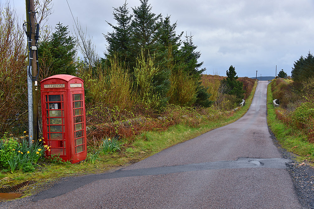 Picture of a red phone box next to a rural single track road