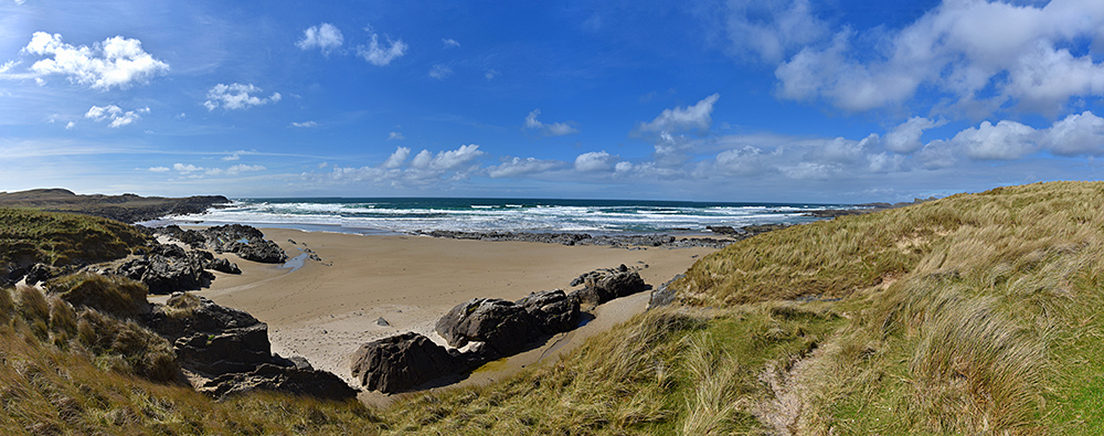 Panoramic picture of a view from a path through dunes to a beach on a sunny day