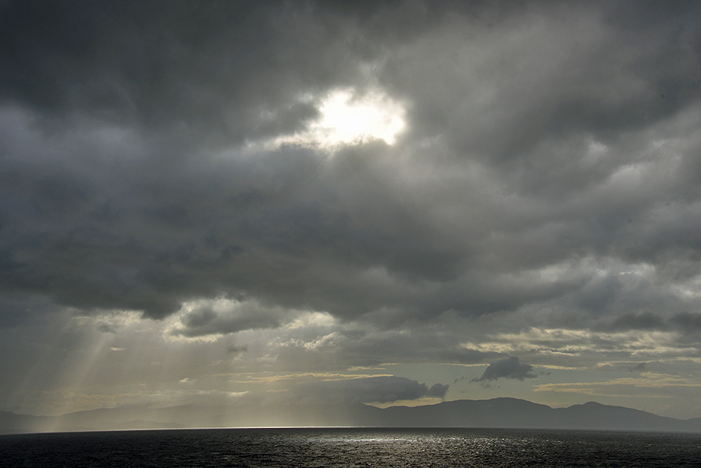 Picture of dramatic clouds with the Sun breaking through over a coastline seen from a ferry