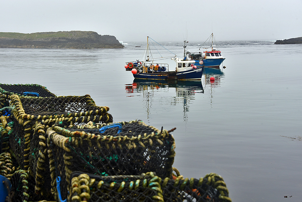 Picture of two fishing boats moored in a bay with two offshore islands, fish baskets stacked on the pier